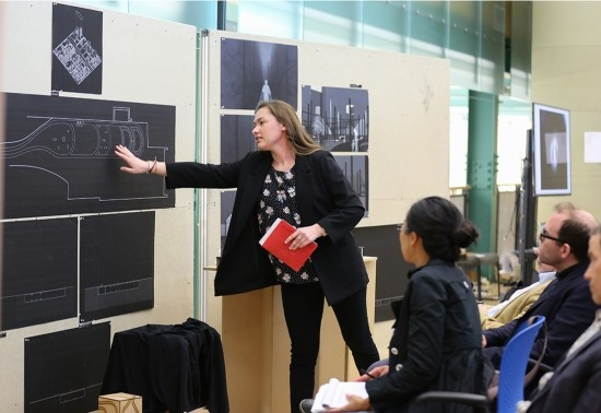 A female architecture presents her pinned up boards during reviews to the jury.