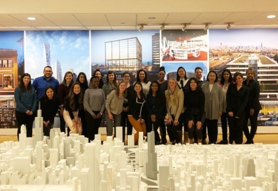 A group of Penn State Master of Architecture students gathered behind an elaborate cityscape model in the offices of architectural firm SOM.