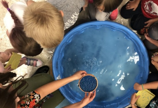 Overhead view of a group of children surrounding a bright blue tub filled with liquid; one student has arms outstretched, holding a copper bowl of what appears to be intense blue dye.