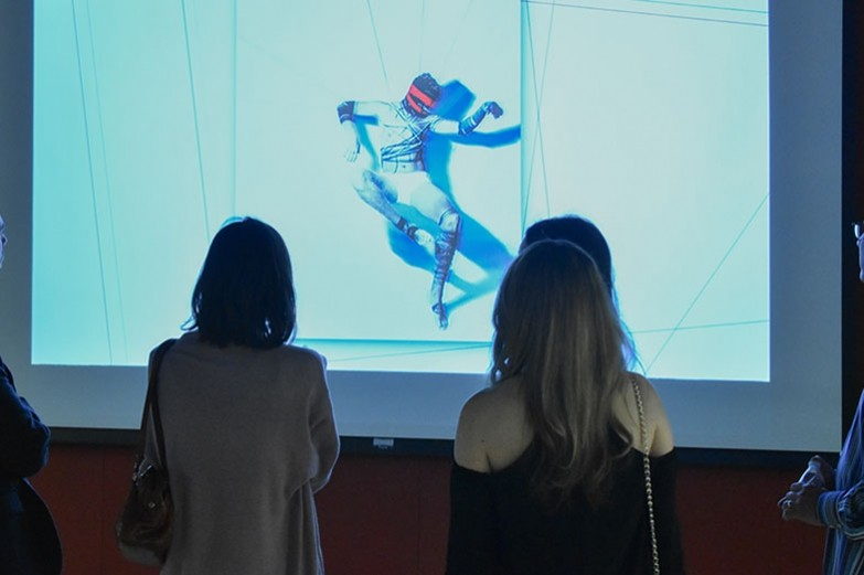 A view of the backs of two women who are viewing a projected image on a screen.