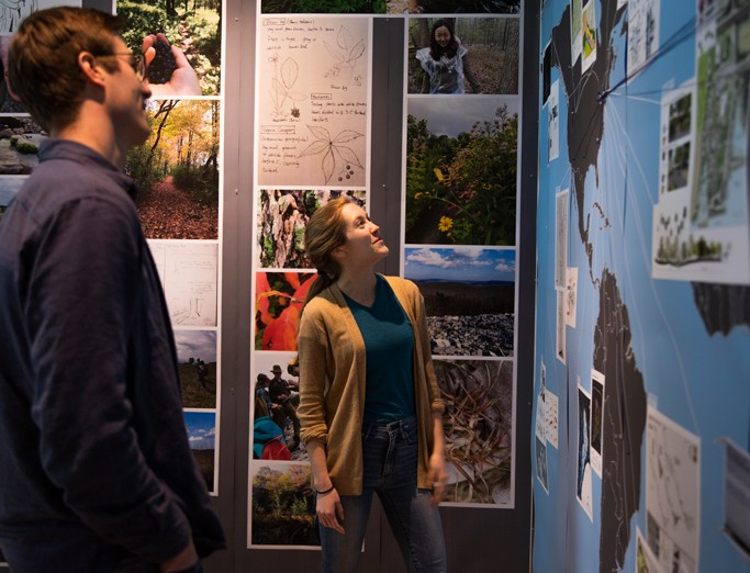 Two students discussing a landscape architecture design project pinned up on wall for review.