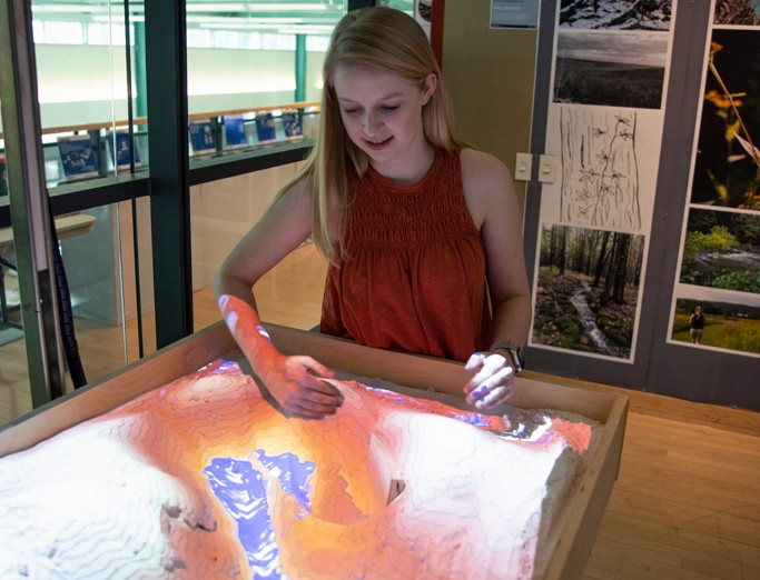 A student moving sand in a sandbox with an overhead projection effect of contour lines and water effect reflecting on the sand during a landscape architecture student display event.