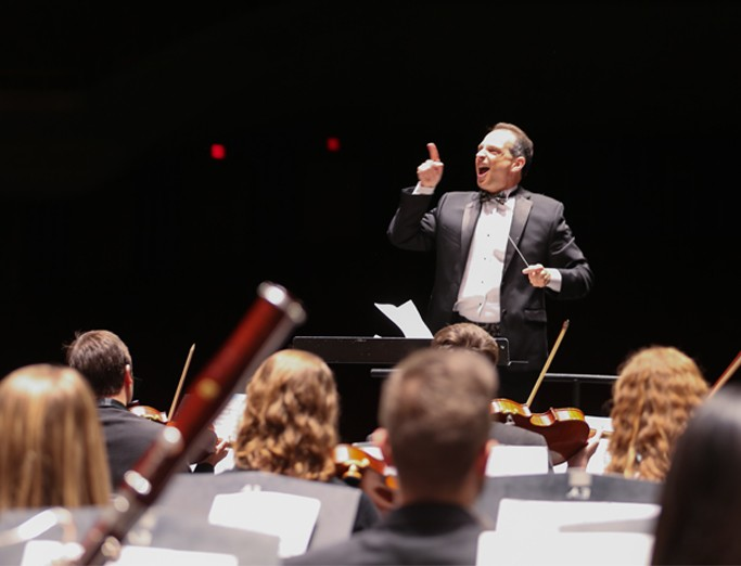 Orchestra performance featuring the conductor.