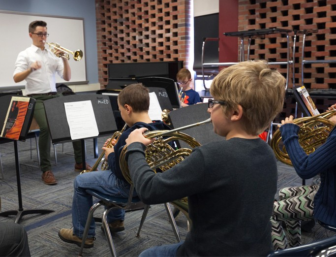 School of Music student teacher helping elementary students during rehearsal.