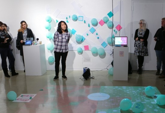 First year M.F.A. student exhibition with an interactive floor projection and teal balloons.