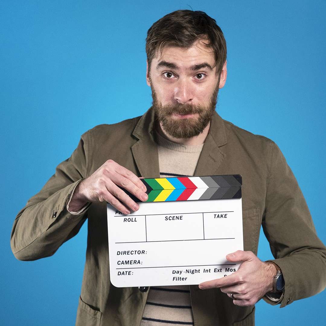 Portrait of Benjamin Andrew holding a clapper square against a blue background.