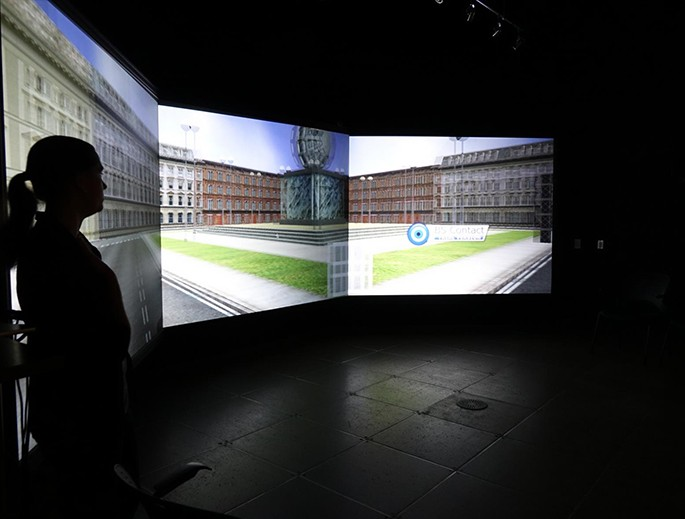 A female student's profile at left against an immersive reality background on a screen behind her in a darkened lab.