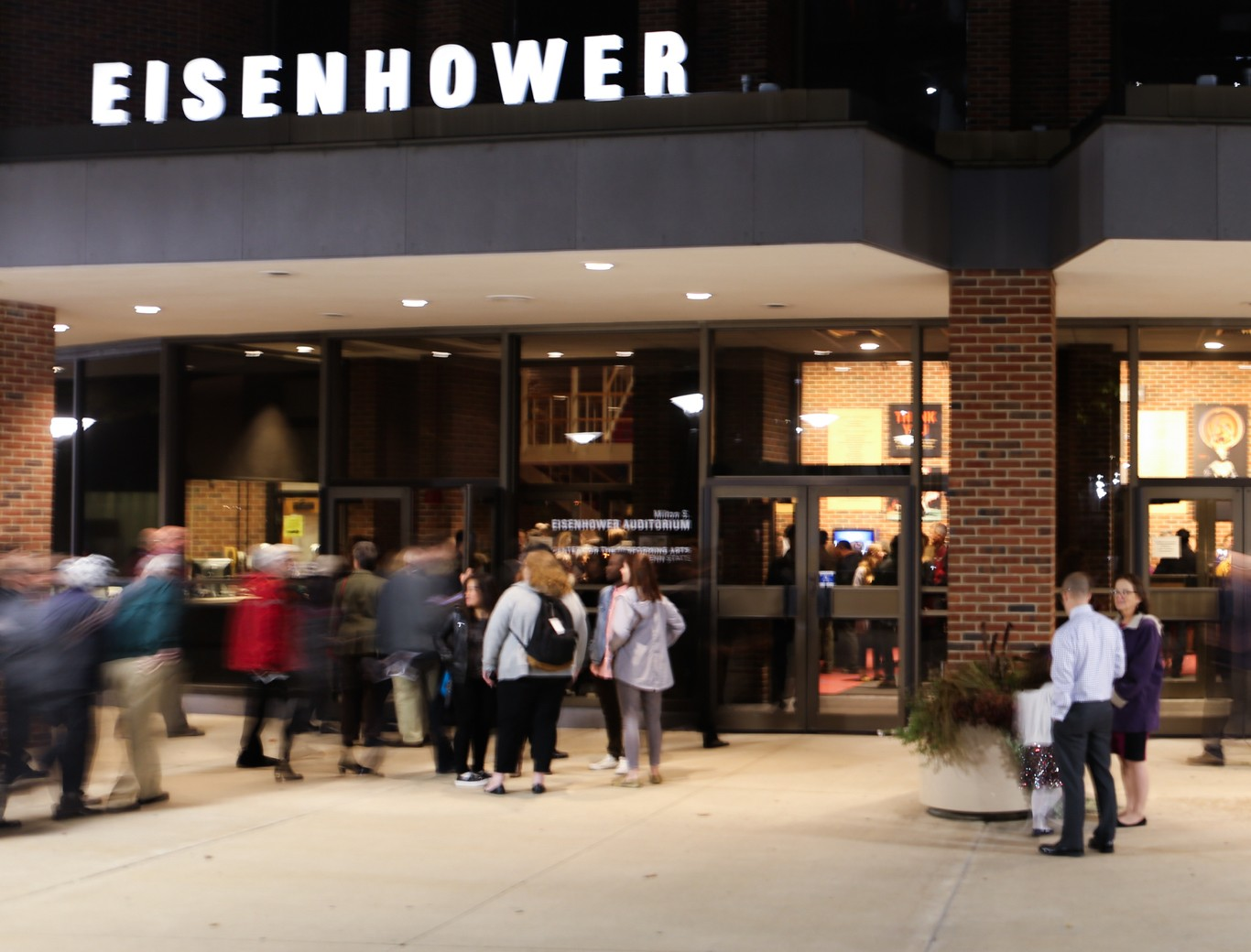 People standing and moving in front of the illuminated entrance to Eisenhower Auditorium