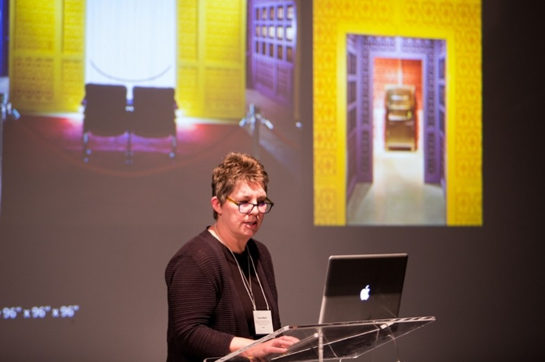 Penn State art professor Cristin Millet presenting in front of brightly colored screen.