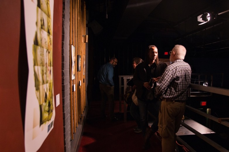 Visitors talking in shadows along a mezzanine-level walkway; close-up of art pieces hung on wall.