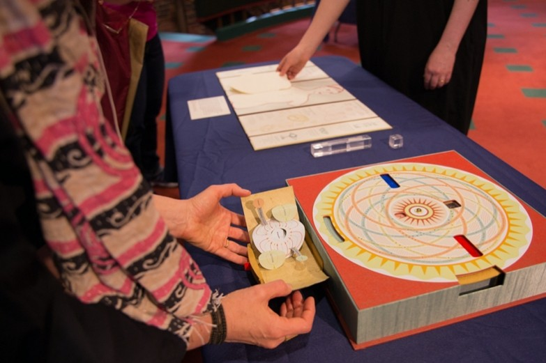 Hands opening a folded paper pop-up with a mandala drawing.