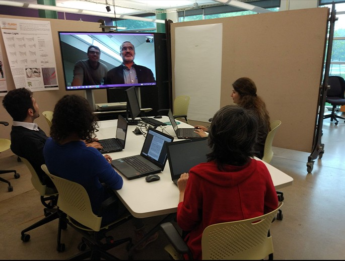 Students sitting around a conference table videoconferencing with a researcher.