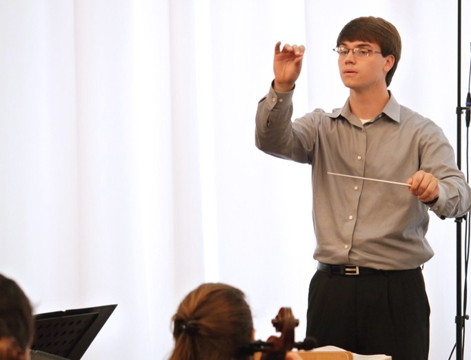 PSU student conducting a music rehearsal.