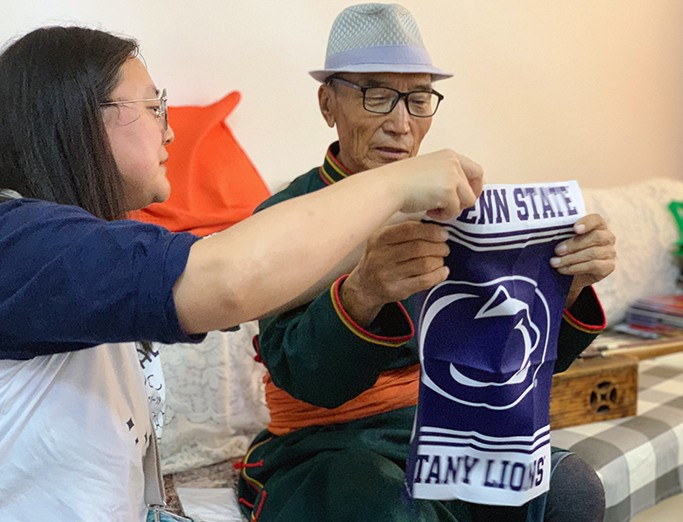 A music education Ph.D. student shows a blue and white Penn State Nittany Lions garden flag to an older individual sitting on a couch.