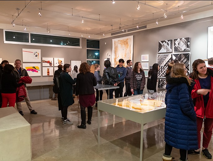 Students and faculty milling around an exhibition in the Rouse Gallery.