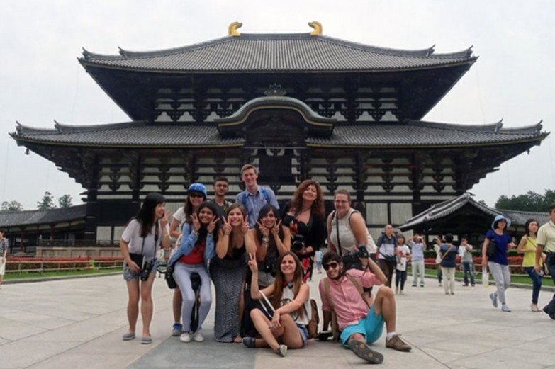 Students posing in front of temple