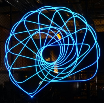 Long exposure photo showing a complex, blue, spiral-patterned light drawing using a 6-axis robot arm; coding and design by Vernelle Noelle