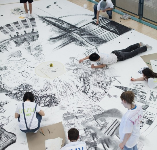 Architecture students working on extremely large format technical charcoal drawing