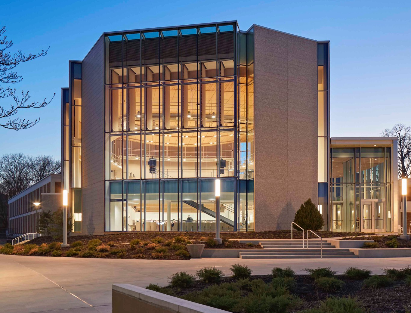 The modern glass facade of Esber Recital Hall illuminating an evening on University Park campus.