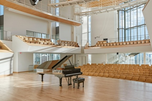 Grand piano on Esber Recital Hall stage, seen from the stage wings.