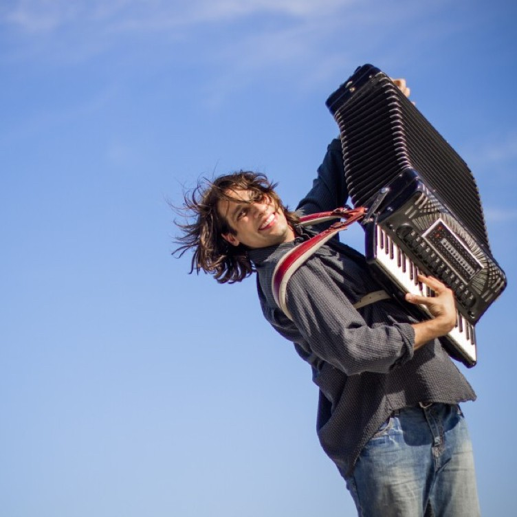Alex Meixner playing an accordion, posing against a blue sky background