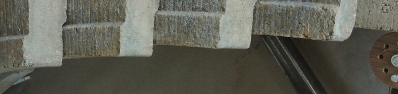 Close-up of concrete arch positioned on its side, supported by a metal frame.