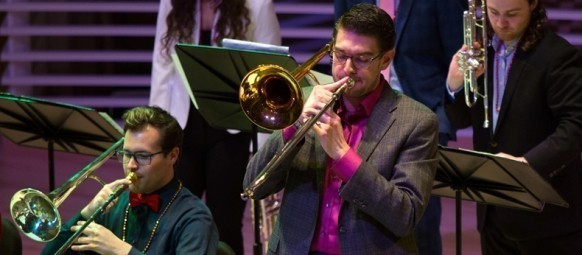 Graduate student in the School of Music playing trombone during a Jazz Festival performance.