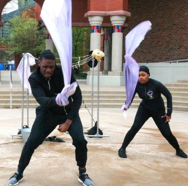Outdoor dance group performance using flags as props in front of the Palmer Museum of Art.