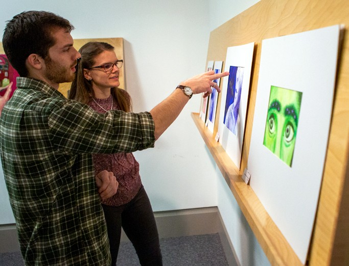Students examining matted artwork on a shelf at the Palmer Museum of Art.