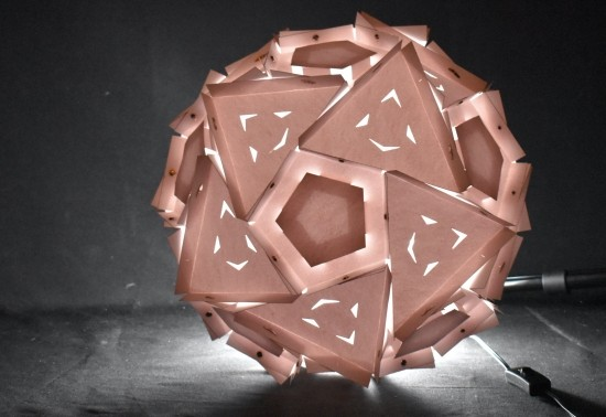 A spherical architectural lantern with light emanating from within a repeating pattern of laser-cut facets.