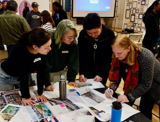 Landscape architecture students and community members looking at designs spread across table at a Community charette in Hazelwood, PA.