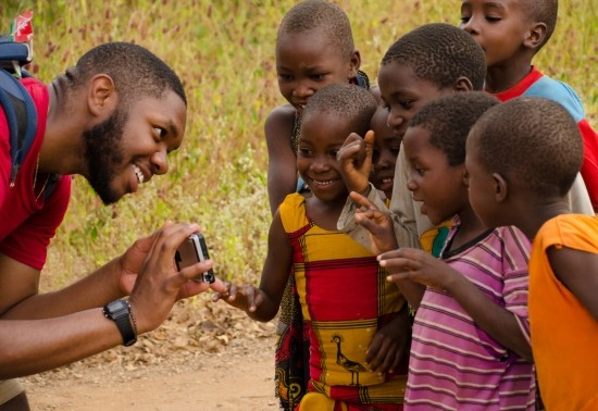 Close-up of Penn State Landscape Architecture student showing a camera to a group of smiling Tanzanian children