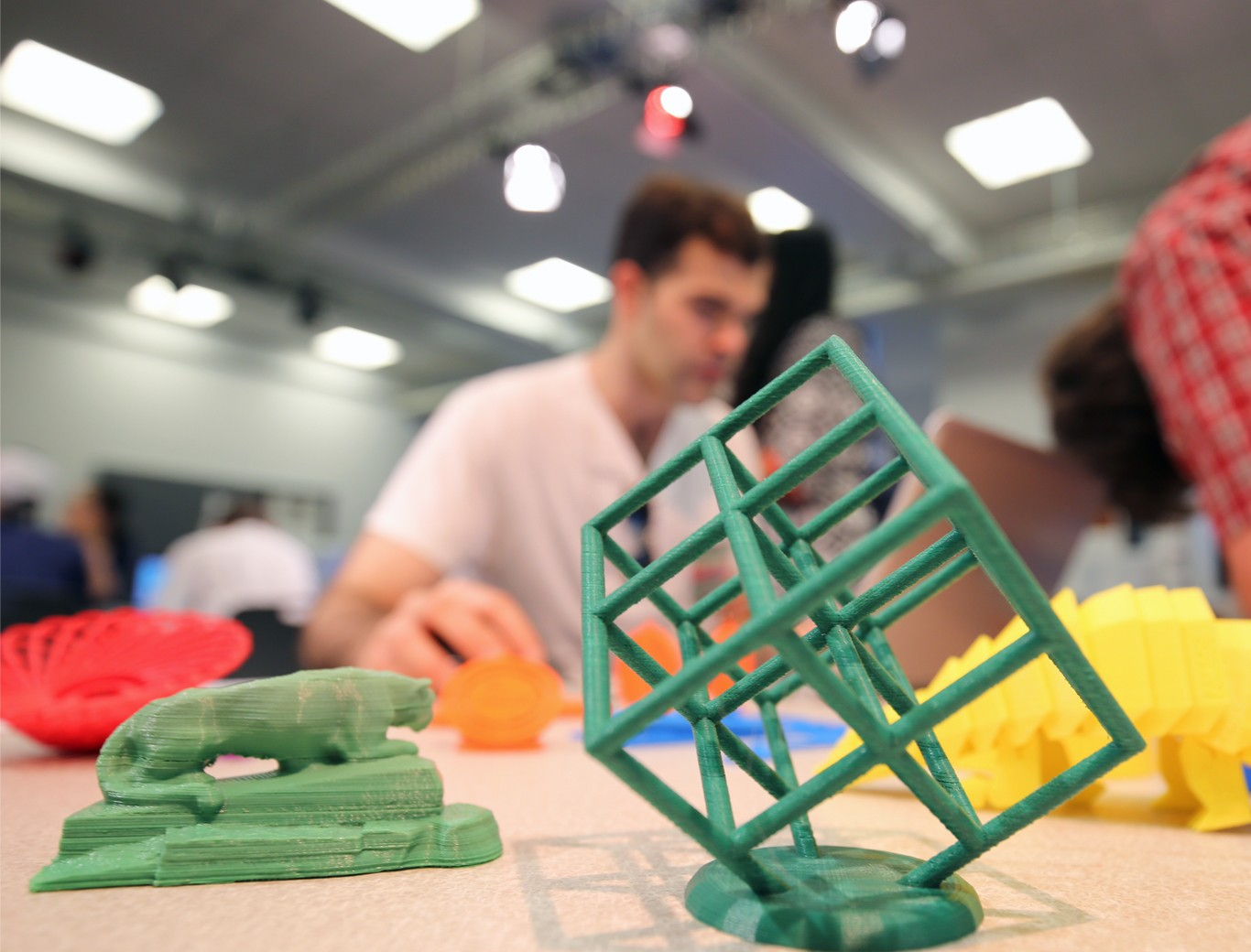 Students participating in Making of the Masses workshop, creating 3D printed objects, such as a cube, the nittany lion shrine, and other bright colored geometric objects.