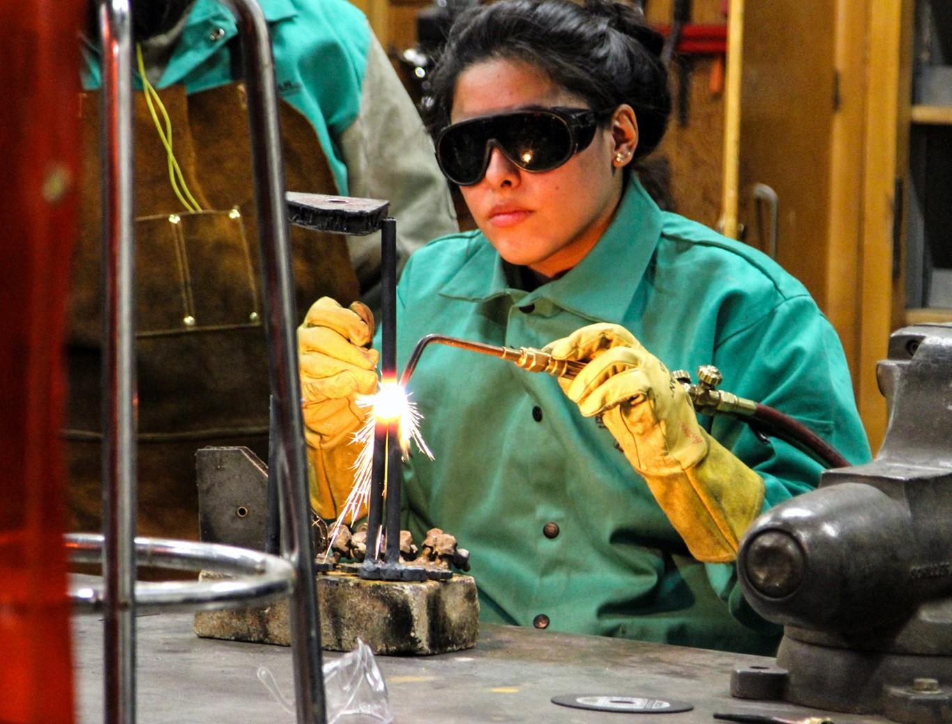 SoVA student using an arc welder fusing metals together.