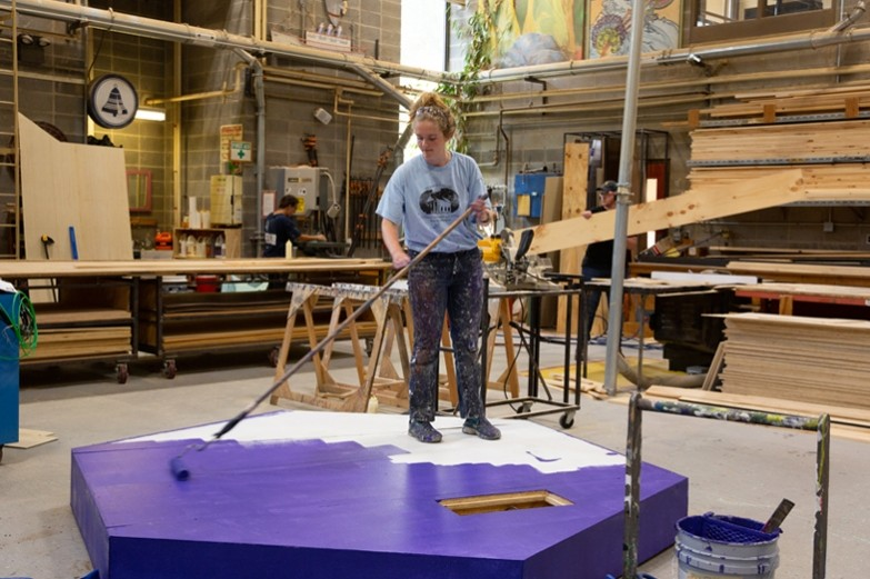 A student painting multiple platforms to be used as props in a School of Theatre production.