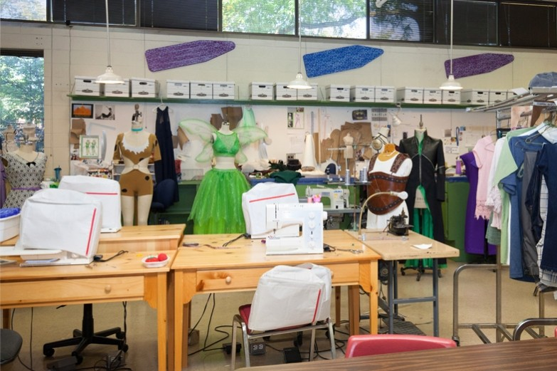 Costume shop showcasing numerous costumes and sewing machine stations.