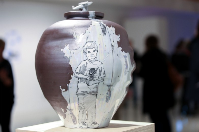 A smooth ceramic vase showcasing a section of it etched away with a detailed illustration of a young boy catching fish.