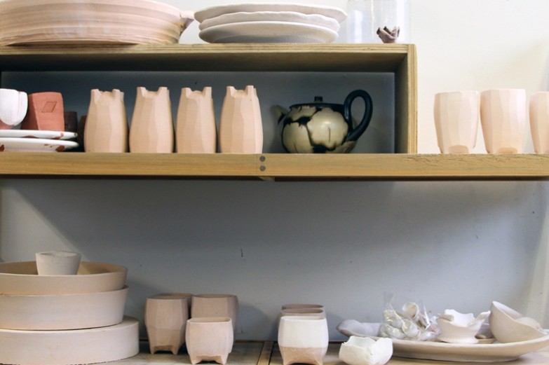 Various pottery objects displayed on wooden racks in the SoVA Ceramics Studio.