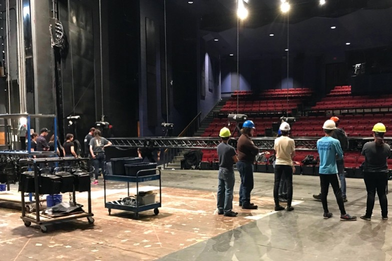 Playhouse Theatre stage crew assembling and reconfiguring lights on stage.