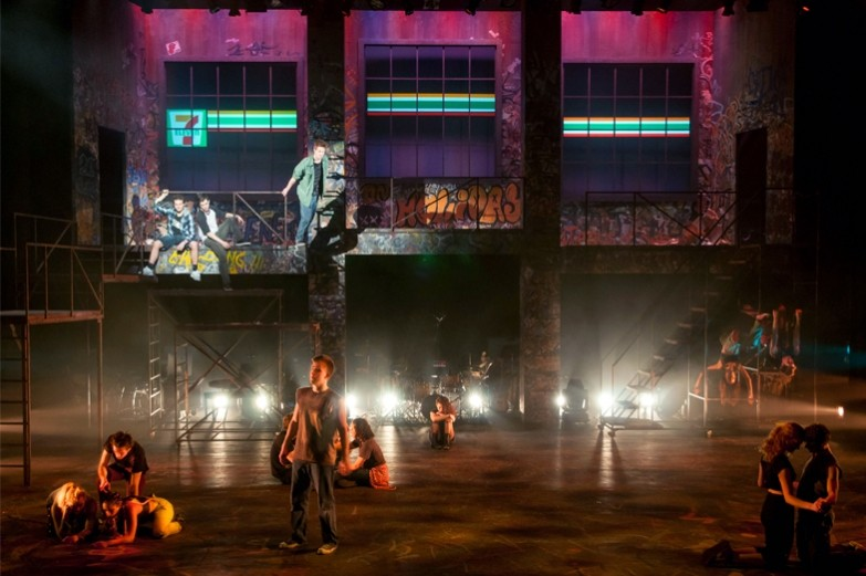 A scene from the production of American Idiot, showcasing a musical number with the ensemble cast singing and dancing on stage and in the rafters.