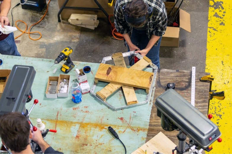 Architecture student drilling a nail into a metal base for a section of a structural wall.