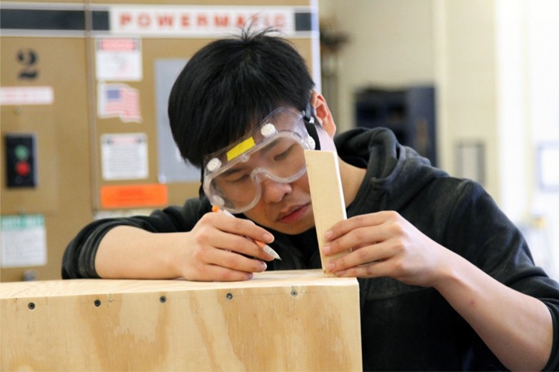 SoVA student centering and measuring a piece of wood to attach to a wooden box.