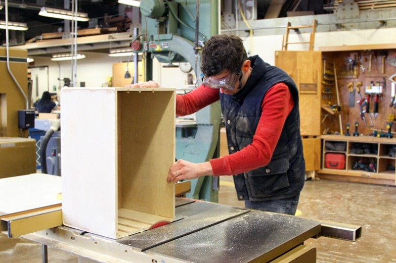 SoVa student using a table circulating saw to even out the edge of a wooden box.