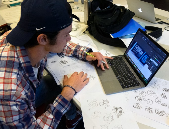 Graphic design student in class working on a logo through various drawings on paper and refiningn on his computer.