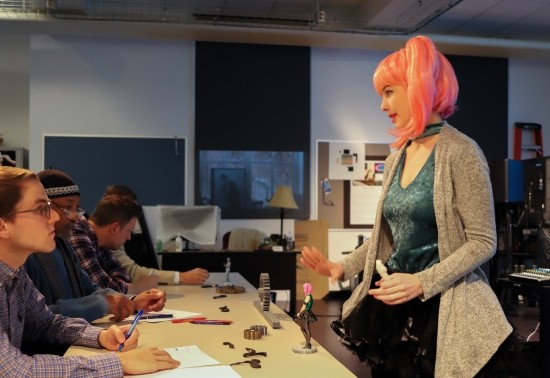 A student presents her 3d model figurine concept to a panel of judges during the Arts Business Ideas Competition. Mimicking the look of her 3d model, she wears a pink ponytail wig and vibrant outfit.