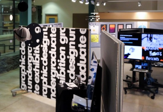 Undergraduate graphic design student work exhibition: showcasing a wall divider with big bold text, digital designs on flat-screen TVs, and poster design pinned up on a divider board.