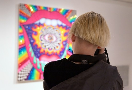 A student photographing colorful artwork on display in Zoller Gallery.