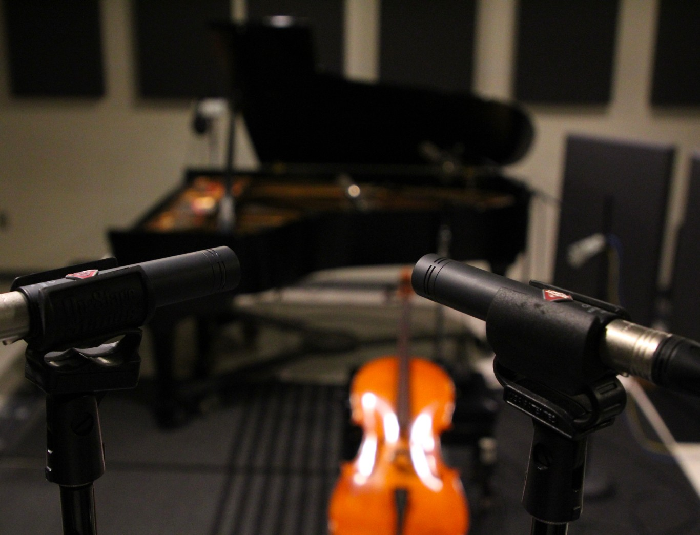 Microphones in the foreground, with instruments and recording equipment in the Penn State ROARS studio.