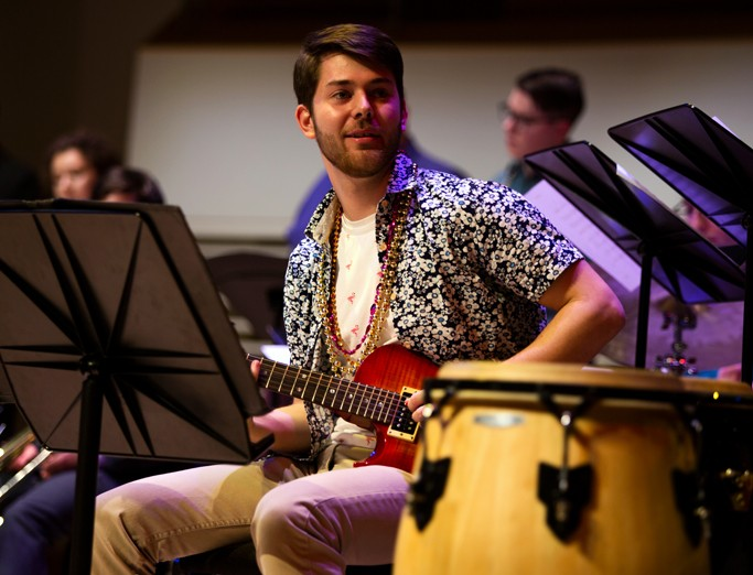 School of Music student playing the guitar on stage during the Mardi Gras Jazz Concert at the Recital Hall.
