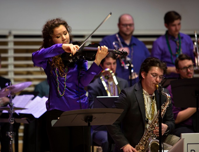 School of Music student playing the violin on stage during the Mardi Gras Jazz Concert at the Recital Hall.
